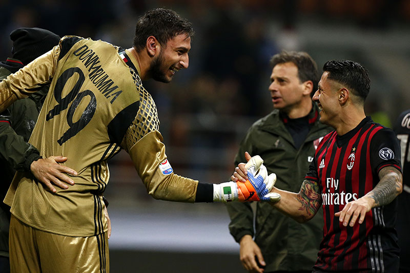 AC Milan's goalkeeper Gianluigi Donnarumma (L) celebrates with AC Milan's forward Giacomo Lapadula after the Italian Serie A football match AC Milan versus Juventus on October 22, 2016 at the San Siro Stadium in Milan. / AFP / MARCO BERTORELLO (Photo credit should read MARCO BERTORELLO/AFP/Getty Images)