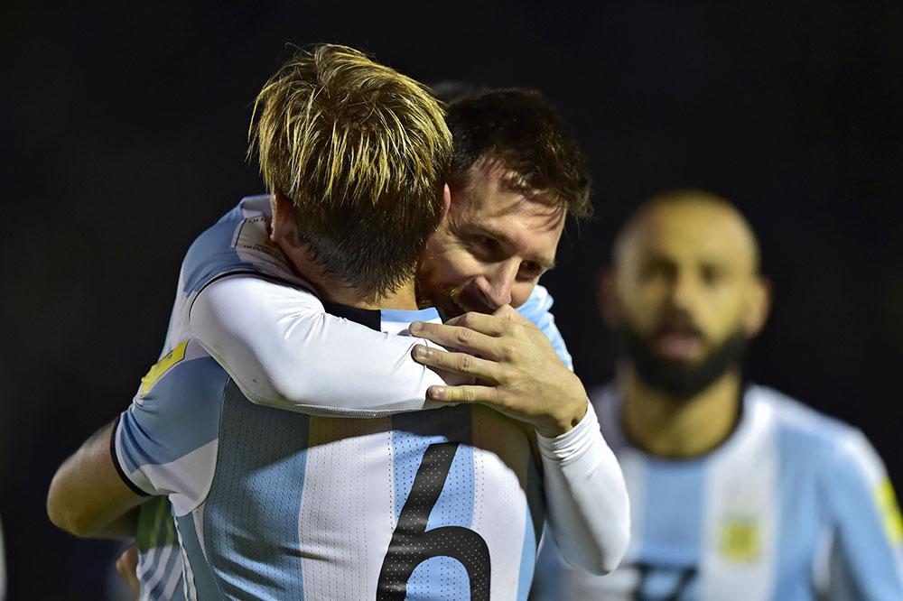 Lucas Biglia and Lionel Messi celebrating during the Ecuador-Argentina FIFA World Cup 2018 qualifier at Estadio Olímpico Atahualpa on October 10, 2017 in Quito, Ecuador. (RODRIGO BUENDIA/AFP/Getty Images)